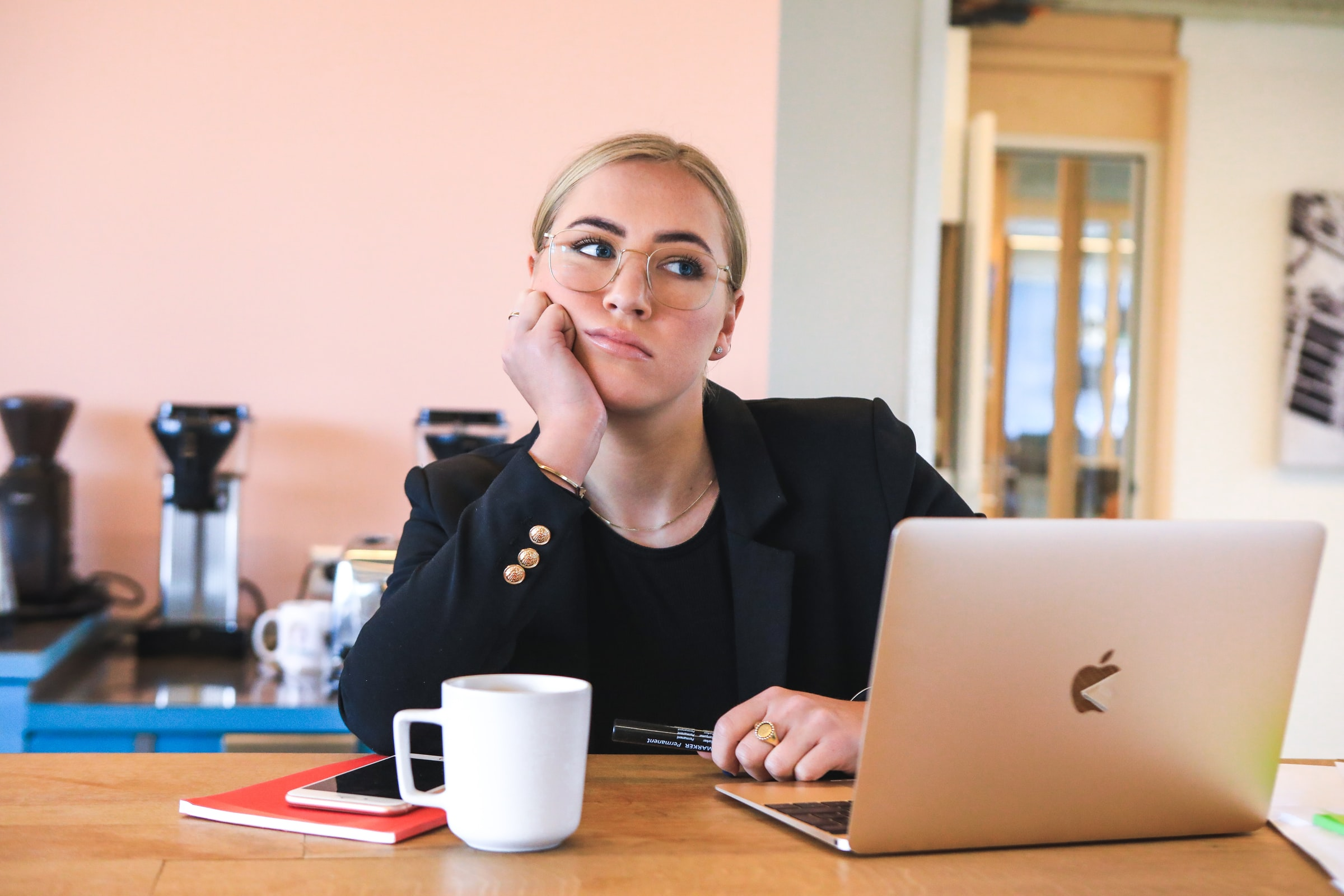 Distracted woman sitting at desk with laptop and coffee cup