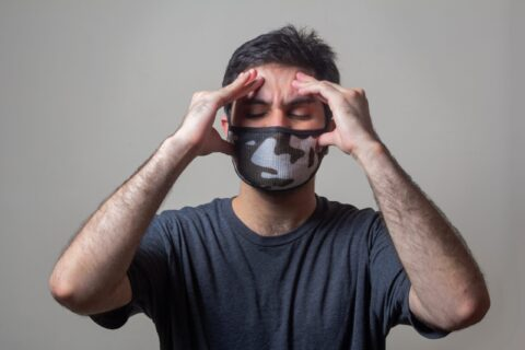 Man with mask holding head