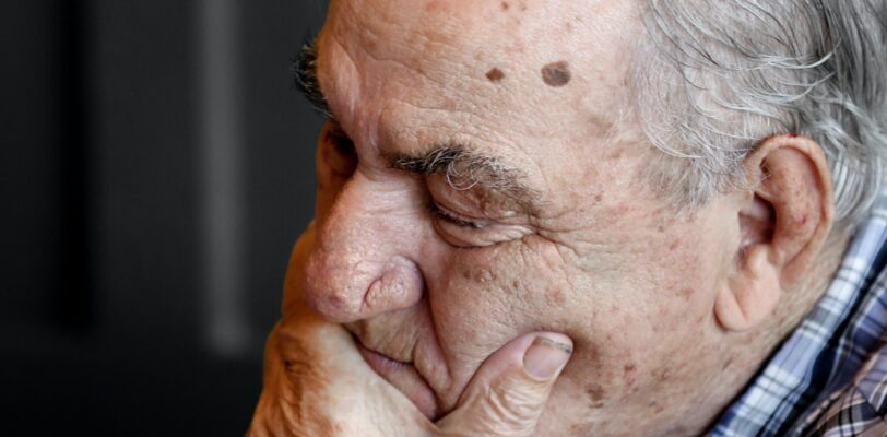 Elderly man covering his mouth with his left hand